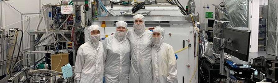 researchers posing in a clean room wearing protective equipment
